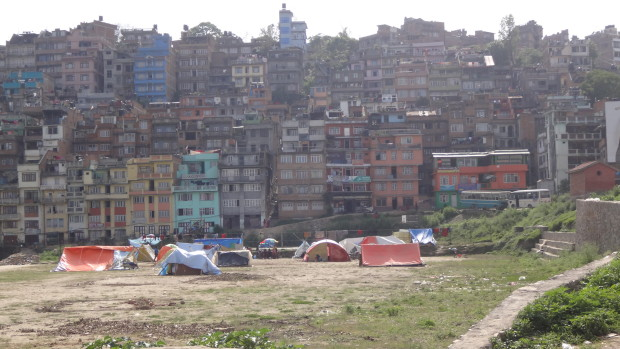 キルティプール市外観(山肌にこぼれんばかりに建つ家々と広場でテントを張り避難する人々)