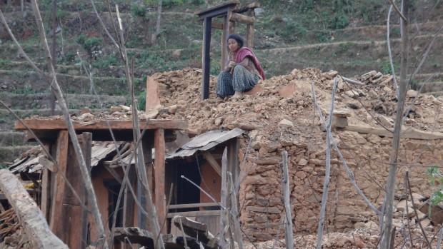 壊れた家の窓際に呆然と座り込む女性。この地区の建物はすべて全壊